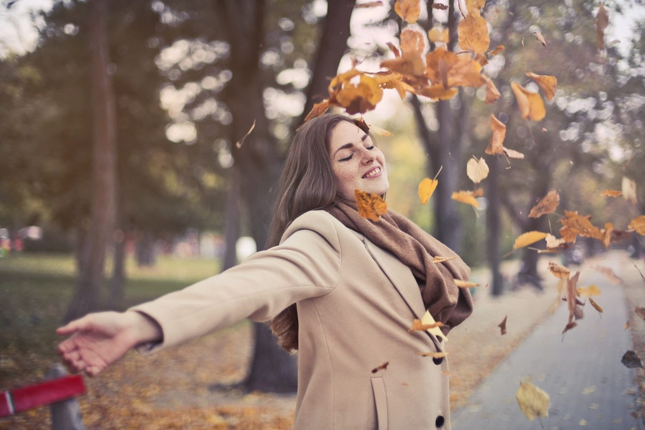 wellness tips for an abundant fall - woman throwing leaves into air